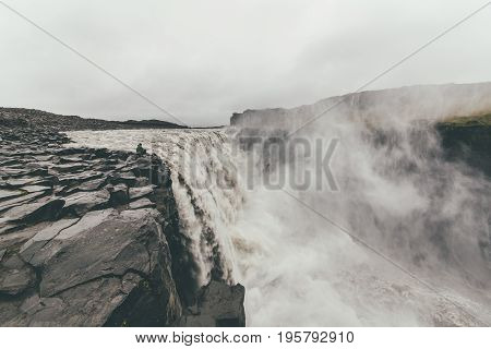 Tourist standing on extremely dangerous distance near Dettifoss waterfall in Vatnajökull National Park in Northeast Iceland.Extreme sports.Adrenalin.Possible accident.Hiking and climbing.
