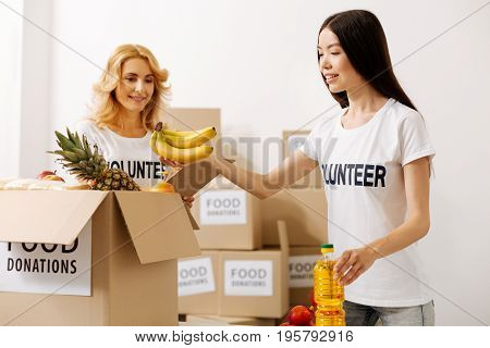 Strong support. Devoted charming charismatic woman checking the items her colleague packing while holding a list in her hands
