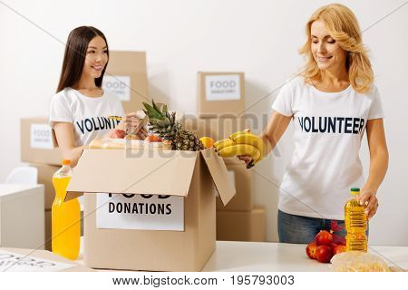 Following instructions. Young attentive energetic woman helping her colleague compiling a parcel while following the list of need products