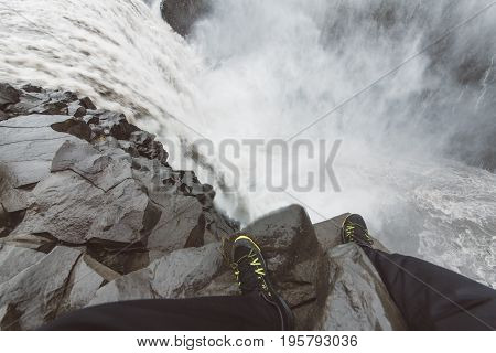 Tourist on extremely dangerous edge distance experiencing powerfull Dettifoss waterfall in Vatnajökull National Park in Northeast Iceland.Kanyon cliff.Powerfull destructive nature.Ring road tour