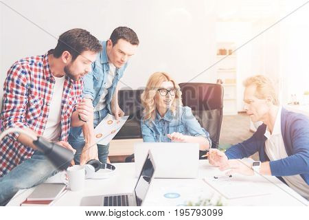 Creative atmosphere. Professional group of designers sitting at the table and discussing project while expressing their thoughts