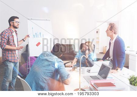 Show the tendency. Professional colleagues analyzing their business and talking about new strategies while working in the office