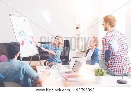Just look. Cheerful woman showing the chart and smiling while talking with her colleagues in the office
