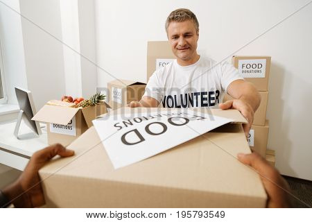 Thank you. Handsome charismatic devoted man taking a box filled with food from nice people while working for charitable institution and shipping parcels to those in need