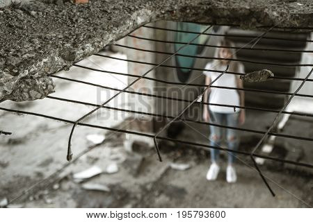 View through the grate. A lonely girl in a white T-shirt and jeans stands on the ruins of a ruined house. Sad expression, a tragic atmosphere. Russia