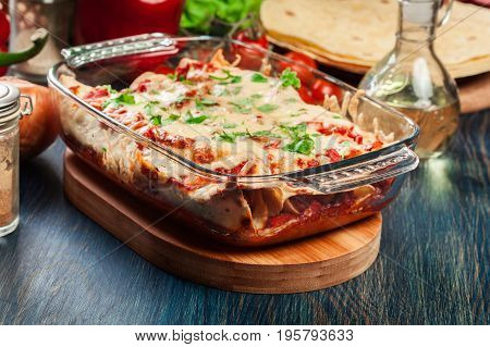 Traditional Mexican Enchiladas With Chicken Meat, Spicy Tomato Sauce And Cheese In Heat Resistant Di