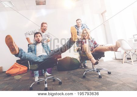 Nice rest. Low angle of cheerful colleagues having fun and riding in chairs in the office