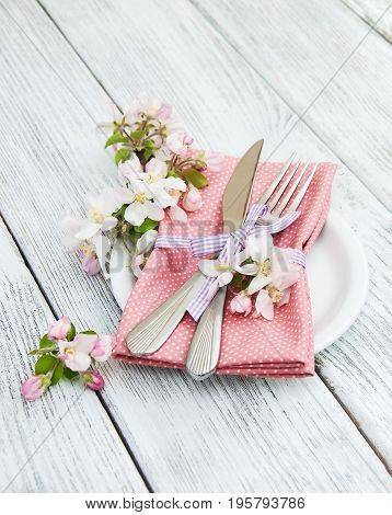 apple blossoms with fork and knife on table