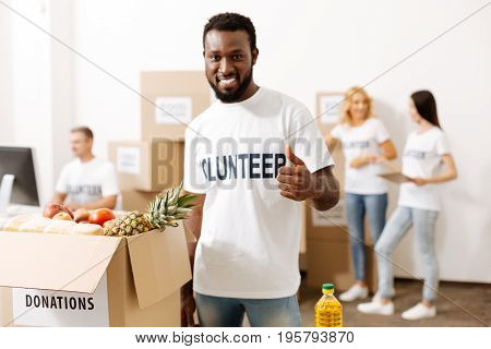 Give back to the community. Young optimistic nice man promoting charity while helping people packing supplies for those in need
