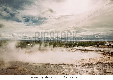 Eruption of Strokkur fountain geyser in a geothermal area in southwest Iceland.Famous eruptive geyser and tourist attraction.Icelandic geothermal features,mud pools,fumaroles and Geysir geyser