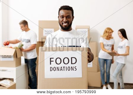 You can do your part. Enthusiastic cheerful persistent guy working for a noble cause and volunteering in charitable organization while shipping food supplies for those in need