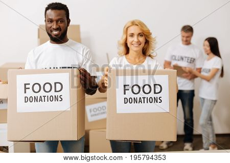 Team of enthusiasts. Admirable enthusiastic altruistic men and women dedicated to noble cause and volunteering in charitable organization while canvassing food donations for the poor