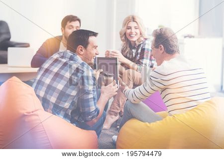 Modern smart technologies, Positive delighted colleagues sitting in circle and using tablet while drinking coffee