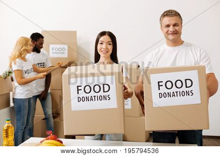 Uniting for greater good. Admirable passionate active men and women dedicating their time to good cause and canvassing food donations for the poor while helping as volunteers