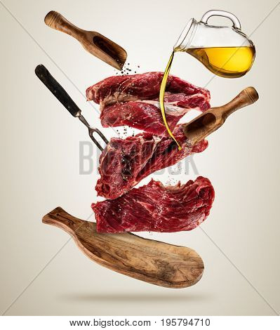 Flying pieces of raw steaks, with ingredients for cooking, served on woodenboard. Concept of food preparation in low gravity mode. Separated on smooth background. High resolution image