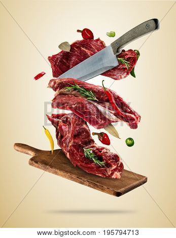 Flying pieces of raw steaks, with ingredients for cooking, served on woodenboard. Knife cutting the meat. Concept of food preparation in low gravity mode. High resolution image