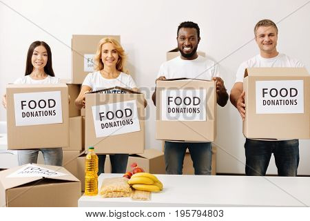 Make yourself useful. Young confident altruistic men and women holding the boxes for collecting food donations they later shipping to those in need