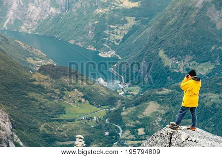 Tourism vacation and travel. Male tourist taking photo with camera enjoying Geiranger fjord and mountains landscape from Dalsnibba Plateau viewpoint Norway Scandinavia.