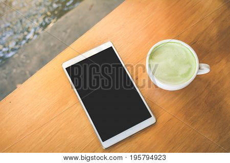 Green tea cup and tablet in cafe shop time to relaxing hipster tone soft of focus