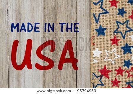 Made in the USA text with USA red and blue stars burlap ribbon on weathered wood