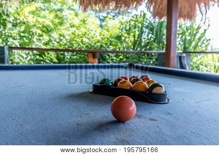 Billiard balls in a blue pool table, game. Outside, tropical cafe.