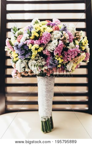 The bride's bouquet is on a chair with a striped back