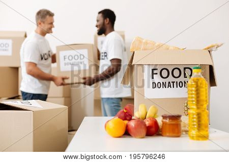 We can manage it. Handsome devoted admirable guys working in a warehouse where donated food being stored and helping moving it pro bono