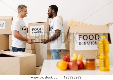 Strength and kindness. Sincere devoted kind gentlemen spending his free time preparing a shipment of goods for the poor while helping his colleague with heavy box