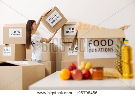 Not so empty package. Devoted helpful confident woman working as a volunteer and moving packages in a warehouse while preparing a weekly shipment