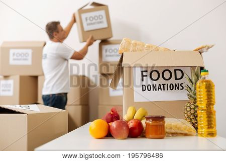 Storage for supplies. Handsome caring attentive man taking a packing to fill with food while preparing a shipment for those in need