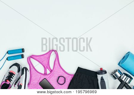 Sportswear With Sneakers, Smartphone, Fitness Tracker And Fitness Equipment Isolated On Grey