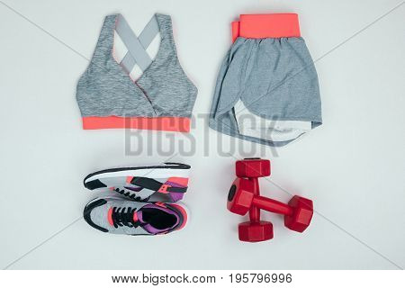 Flat Lay With Sportswear With Sneakers And Dumbbells Isolated On Grey