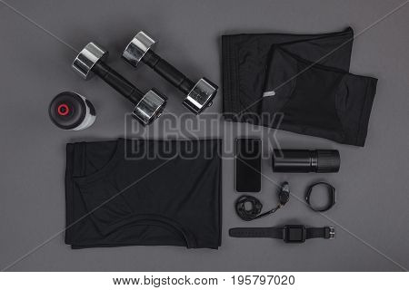 Top View Of Sportswear, Dumbbells And Digital Devices Isolated On Grey