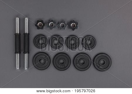 Top View Of Various Metal Barbells And Weight Plates Isolated On Grey