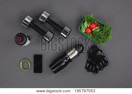 Flat Lay With Smartphone With Fitness Tracker, Dumbbells And Vegetable Salad Isolated On Grey