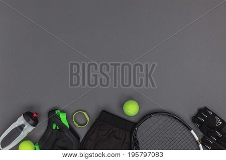 Top View Of Tennis Equipment And Sportswear, Fitness Tracker And Sports Bottle Isolated On Grey