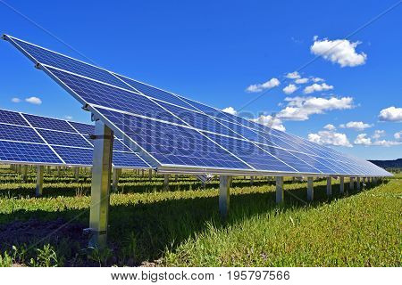 Solar panels on field. Clear sky with a few small clouds on background.