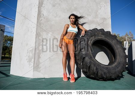 Beautiful young woman in bright sexy shorts with pretty athlete muscular body posing near big tire for exercise. Cross training urban area street gym city workout routine healthy lifestyle.