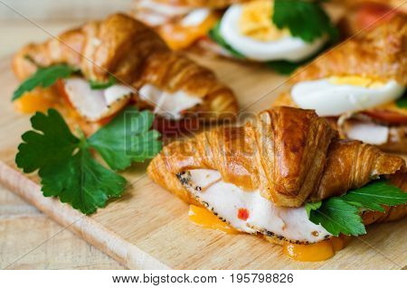 Mini sandwiches with butter croissants chicken meat ham green parsley leaves melted cheese eggs and tomato served on wooden cutting board. Hot breakfast sandwich