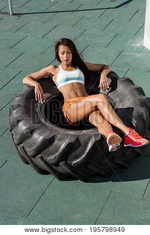 Beautiful young woman with long legs in bright sexy shorts with pretty athlete muscular body rest in big heavy tire. Cross training urban area street gym city exercise routine healthy lifestyle.