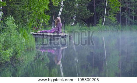 Young woman doing yoga exercises on the lake shore. Urdhva mukha svanasana