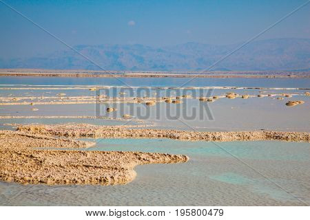 Hot summer day at the famous seaside resort on the Dead Sea, Israel. The shallow sea is covered with evaporated salt. The concept of medical and ecological tourism