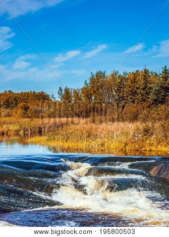 Foam water rapids on the smooth stones of the Winnipeg River. Warm autumn day. The concept of travel