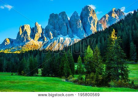 The sunset illuminates fabulous jagged rocks of Tirol and green forest. The Dolomites. The concept of eco-tourism in Alpine meadows