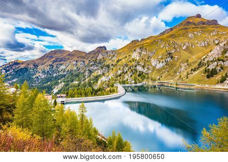 Magnificent glacial lake Lago di Fedaia in the Dolomites. Cloudy cold autumn day. The concept of ecological and extreme tourism