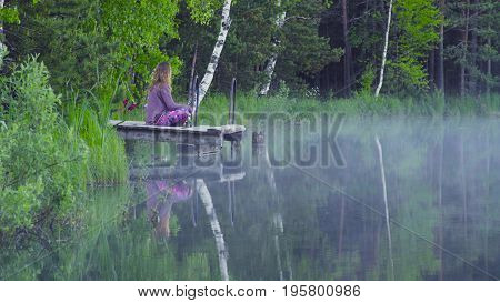 Young woman meditating on the shore of a forest lake early in the morning.
