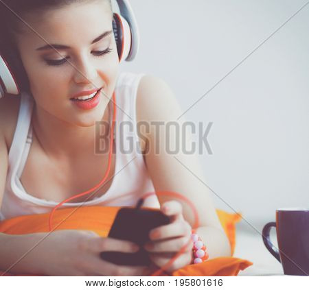Young woman lying on floor and listen to music