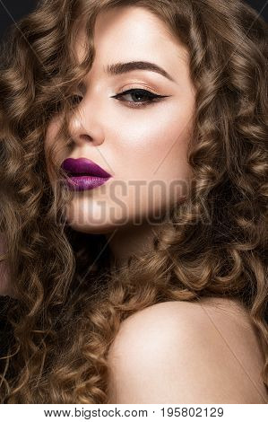 Beautiful brunette girl with a perfectly curly hair, and classic make-up. Beauty face. Picture taken in the studio on grey background.