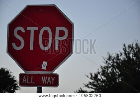 A stop sign in the foreground with a faint sun set in the background