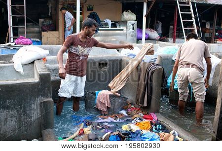 MUMBAI, INDIA - JANUARY 12, 2016: Indian workers washing clothes at Dhobi Ghat a well know open air laundromat in downtown of Mumbai in Maharashtra State